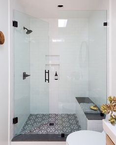 Black hardware and subway tile idea. I like the glass shower walls. The shower a curb, like we want as well. We would like a rain shower head, along with a separate handheld option. I also like the patterned tile on the floor of the shower.