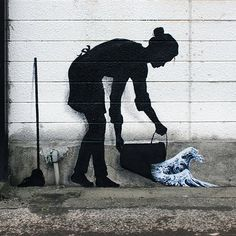 "Silhouette of a cleaning lady pouring out a bucket of Hokusai's iconic ""The Great Wave Off Kanagawa"" left by Spanish street artist Pejac, appropriately in Kanagawa."