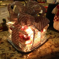 A glass cube, ornaments, Christmas lights and ribbon makes for a great Christmas decoration
