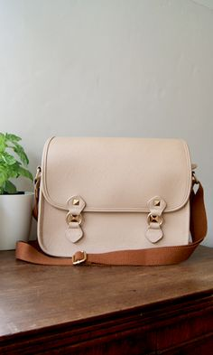 Rose-gold studs give this eggshell pink messenger bag a cool girl edge.