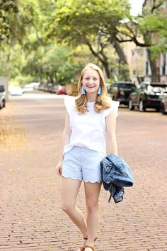 Blue scallop shorts, white flutter sleeve top with blue tassel earrings. Keep warm with a denim jacket.