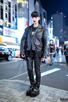 18-year-old Chikio on the street in Harajuku wearing a resale leather biker jacket over a Neon Genesis Evangelion t-shirt, leather pants, and Yosuke platform creepers.