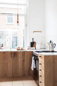 Azulejo branco backsplash, bancada de mármore, paredes brancas, estilo escandinavo. O antes e depois da reforma da cozinha por Holly Marder e Hedda Pier
