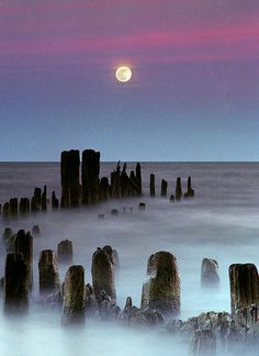 The full moon rises Lake Michigan as rolling waves wash over the remnant of a pier.
