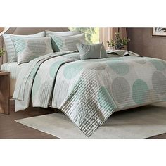Knowles Set features a circular pattern in different shades of gray and aqua covers the soft grey coverlet. Coordinating sheet set included. Set includes coverlet, 2 pillow shams (1 twin), flat sheet, fitted sheet, 2 pillow cases (1 twin)