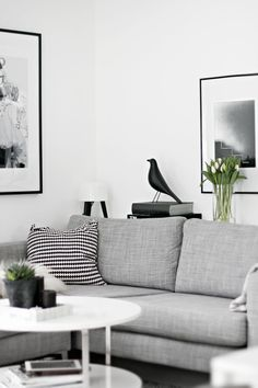 Gorgeous monochrome living room but the elegant finishing touches of large framed prints and flowers are perfect.