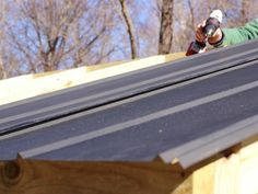 """Roofing is available in corrugated or ribbed styles make of galvanized steel or polycarbonate in a variety of colors. Here we use ribbed steel roof panels painted black. Cut panels to length and start at one end to attach panels one at a time using roofing screws. Allow an overhang of 1-½"""" on the sides, 4 inches at the front and 2-1/2 inches at the rear. Make sure the roof is square with the frame when attaching the first roof panel. Use raised ribs to overlap each panel with the prev..."""