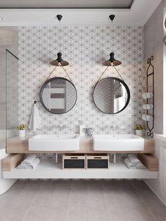 Un meuble double vasque surmonté de deux miroirs ronds.