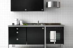 Es un mueble para la cocina de color negro y gris de acero y cerámica. Se compone de un horno, un fregadero, una puerta, tres cajones y un aparador
