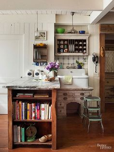 Give new life to old fixtures and furniture to add collected charm to your vintage kitchen. In this room, pieces of salvaged marble serve as a counter atop a cabinet base built from reclaimed wood. French tiles create a colorful backsplash above a hospital sink set among an antique desk and aged office hutch that now holds cups./