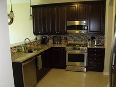 espresso cabinets, stainless steel appliances, and tile backsplash