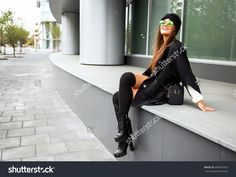 Outdoors fashion portrait of cheerful pretty girl sitting to the street. Smiling, walking, going shopping. Wearing stylish black coat, turban, leather boots, bag and colored sunglasses. Bright make up