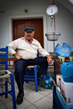Portrait in of an older man at a market in Santorini island, Greece © John Bragg Photography