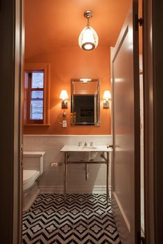 bathroom with orange ceiling and black and white tile