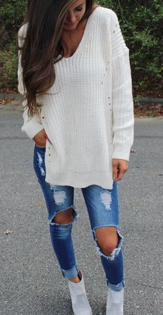 light gray booties ripped jeans and a white split sweater