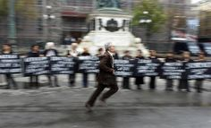 A man runs as protestors hold placards marking the 20th anniversary of the start of the Bosnian war in Belgrade April 6, 2012.   REUTERS/Marko Djurica