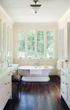 Such a great bathroom!  Dark wood floors anchor white walls and cabinets, while the freestanding bathtub is washed with light from window wall. - Bath Bliss | Atlanta Homes & Lifestyles  2007 Bath of the Year: New construction PRITCHETT+DIXON