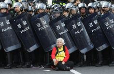 A woman sits in front of riot police blocking the road to protect protesters during the anti-government protest on April 24, 2015 in Seoul, South Korea. Korean Confederation of Trade Unions (KCTU) went on a general strike in protest against the South Korean government's policy, including reformation of the labor market and public pension system. The rally was also joined by other civic groups in Seoul and familie | Chung Sung-Jun/Getty Images