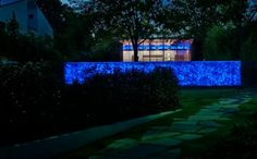 modern garden with a gabion wall decorated with blue LED lighting