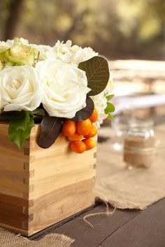 Love this  white centerpiece with pops or orange. Rustic and elegant. Photos by Joan Allen via junebugweddings.com