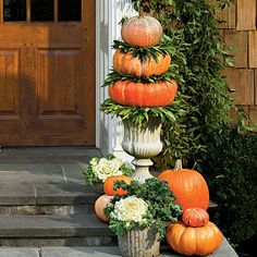 Vertical displays make a big statement at the front door. Tucking in cool-weather edibles such as ornamental flowering cabbages, kale, and bay leaves adds a distinctive twist. To create topiaries, sandwich bay wreaths between pumpkins stacked in concrete urns, and top with a small pumpkin