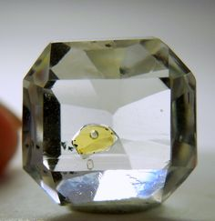 A beautiful square colorless and gemmy Quartz with a small cavity filled with yellow Petroleum.  It has a small bubble that moves around. Really fun with a loupe. It weighs 5.10 carats.