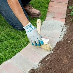 With the bricks set, pour polymeric sand over them and use the brush to sweep it into the spaces between them