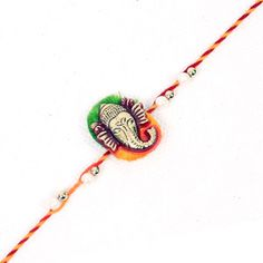 Giftblooms.com showcases this impressive Rakhi thread in its store. This excellent Rakhi thread comes with a satin base with two color combinations green and yellow, which is decked with a symbol of Lord Ganesha. This gives the Rakhi thread a traditional look. Both the sides of the Rakhi thread is decorated with white and golden balls. You can also pair other items available in the site which you can send as Rakhi to India.