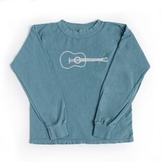 A simple acoustic guitar is screened in white on a super soft, high quality, ice blue, long sleeve t-shirt by Comfort Colors. This shirt is a white, pre-shrunk, 100% cotton, 5.4-ounce children's t-shi