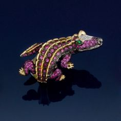 A pink sapphire novelty ring  Modelled as a crocodile with a pink sapphire body and legs, brilliant-cut diamond detail to the head and demantoid garnet eyes.