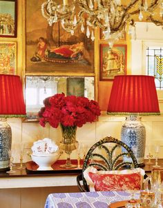 A pair of Chinese lamps with lipstick-red Irish wool shades adds pop to the dining room bistro table, strewn with 19th-century Venetian champagne glasses. A collection of sequined Indian prints from the same era enlivens the wall.  Lynn von Kersting