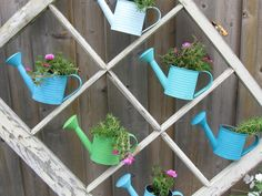 Love the simplicity of this old window frame repurposed as a feature garden with watering can planters. What else would you use? | The Micro Gardener