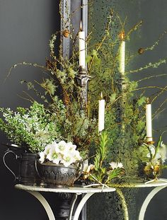 This lovely rustic arrangement uses woodland elements in white and green accented with candles.