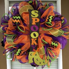 This wreath is made with purple and orange mesh, lime mesh ribbon, chevron printed ribbon, deco tubing and a Halloween sign in the middle.