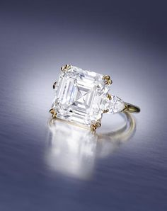 An important diamond ring, Harry Winston, 1986, set with a square emerald-cut diamond, weighing 8.30 carats, flanked by pear-shaped diamonds; signed Winston 8.30, accompanied by a signed pouch. (=)