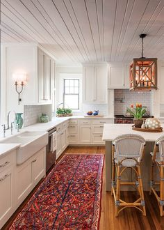 To enhance the breezy, open feel of this #kitchen, the stained wood ceiling- which is original to the house- was painted white. See more of this beautiful #cottage in our Summer Issue!