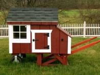 """The """"Push It"""" Coop is a compact and easily portable structure that is ideal for 3 to 5 chickens and available in Barn Red Duratemp siding with white trim and a black shingle roof."""