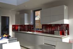 This fused glass splashback features in a house in Hamble, Hampshire. Aside from the amazing view out over the Solent, which you can see in one of the images, inside there is an even more uplifting sight. As you can see, this red dalaman with black and white accents adds a splash of colour to the modern kitchen, and with the light streaming in from the windows, it provides a layered and textured background that just provides that extra wow factor to an already amazing looking view.