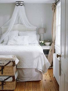 Salvaged Style :: A romantic corona sends a cascade of sheer fabric tumbling over an intricately carved headboard in this dreamy bedroom. The corona started out as an old lamp -- its sockets were removed in favor of a lining of mosquito netting. Side tables fitted with chicken wire add rustic functionality.