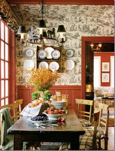 Jane Moore's breakfast room has a charming black and white toile mixed with red paneling. Rustic table, more transferware mixed with creamware.