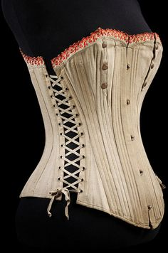 1875-1899 Maternity/Nursing Corset? Made of cream cotton with red machine-embroidered trim. Made in four parts, they fasten at the front with a busk of five metal loops and studs, and at the back they have 17 sets of metal bound eyelets for a laces. At each side there are 12 further sets of metal bound eyelets which fasten with elasticated laces. There is a vertical opening at each breast which fastens with three bronze gilt press studs…