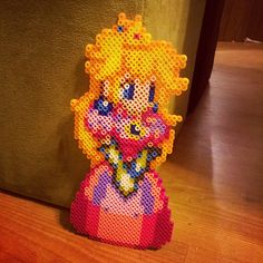 Peach from Mario perler sprite.  This is fancier than the other Peach (Princess Toadstool) I did before, but it looks really nice!  She is pretty time consuming, but worth it.