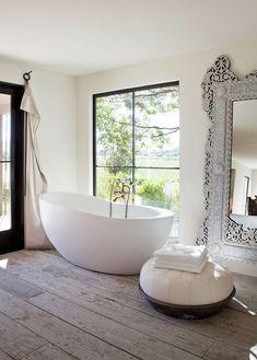 Baignoire ovale, miroir indien, rideau, grands carreaux fenêtre