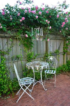 Chippy metal Frrenchie bistro table, pink roses and old candle chandy - love this space!