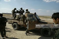Armed men in uniforms identified by Syrian Democratic forces as US special operations forces stand in the back of a pickup truck in the village of Fatisah in the northern Syrian province of Raqa on May 25, 2016. US-backed Syrian fighters and Iraqi forces pressed twin assaults against the Islamic State group, in two of the most important ground offensives yet against the jihadists. The Syrian Democratic Forces (SDF), formed in October 2015, announced on May 24 its push for IS territory north…