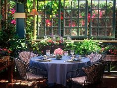 A variety of colorful plants and potted flowers add drama to this feminine garden space. Set the table in florals and pastels for a cozy brunch.