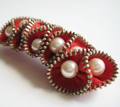 Made from new metal zippers and  backed with pin back.    It is accented with a pearl beads.    Measures approximately 3 X 1.25 inches. Item will ship