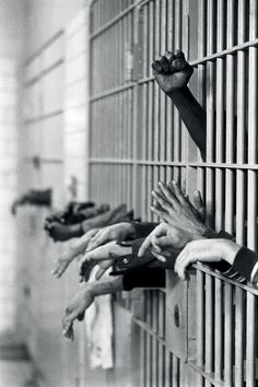 From Photographer's Paradise by Jean-Pierre Laffont.  Manhattan, New York City, NY. September 28th, 1972.  Hands from behing the bars at Toms Prison. Standing on Center Street at Leonard Street, and was built in 1840 with granite from the old Bridewell Prison in City Hall.