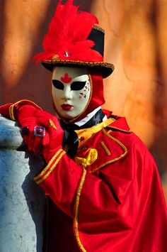A red masked man poses outside a monastery near the Arsenale di Venezia during Carnival in Venice, Italy