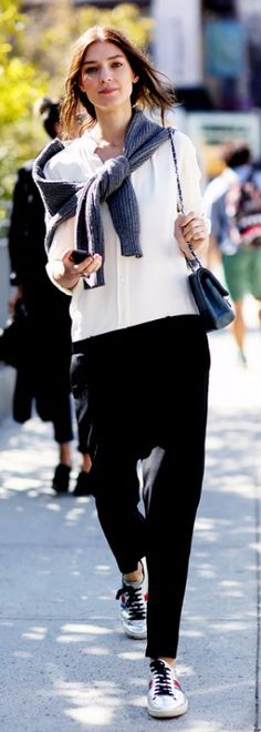 Loose white blouse and black trousers with a grey knit around the shoulders
